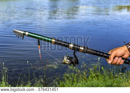 Male Hand Holds Spinning On The Background Of Muddy Freshwater Of A Lake, River Or Pond. Folding Fis