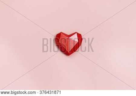 Red Polygonal Paper Heart Shape On Cream Colored Background. Holiday Background With Copy Space For