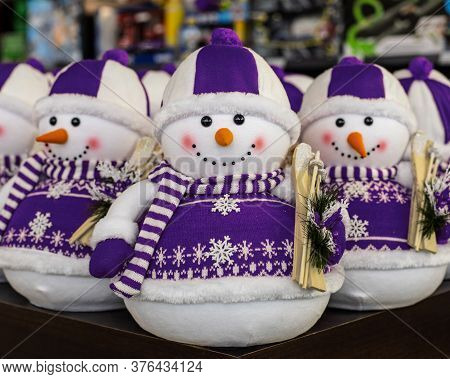 Toy Snowman In A Purple Lilac Sweater And Ski Hat. New Year Decorations, Holiday Toys. Christmas Car