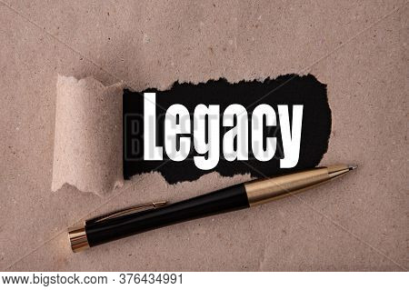 Legacy Text Written Under Torn Paper And A Recumbent Metal Pen. Business Strategy Concepts.