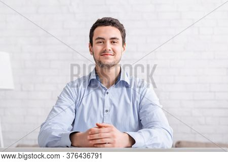 Video Conference From Home. Official Smiling Guy In Shirt Sits At Table On White Brick Wall Backgrou