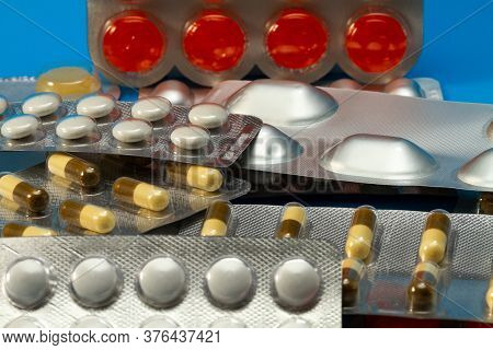 A Pile Of Pills In Blister Packs Close Up. The Blister Pack Is Full Of Multi-colored Tablets. A Pack