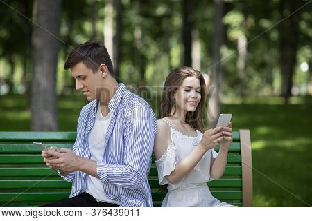 Gadget Addiction. Millennial Couple Busy With Their Smartphones, Talking To Virtual Friends And Igno