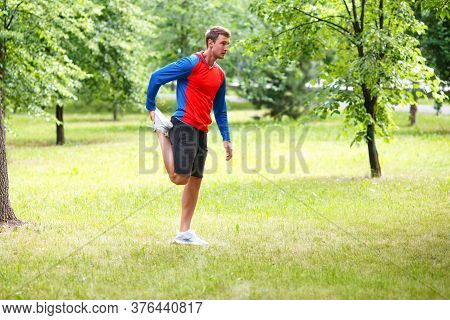 Sport And Healthy Lifestyle Concept - Male Jogger Stretcing Muscles In Public Park.
