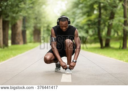 Black Sportsman Getting Ready For Morning Exercising In Park, Tying Shoelaces. Outdoor Workout Conce