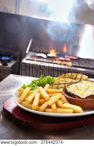 Shot Of A Lasagne Verdi With Chips And Side Salad And Garlic Bread Served In A Plate In Restaurant K