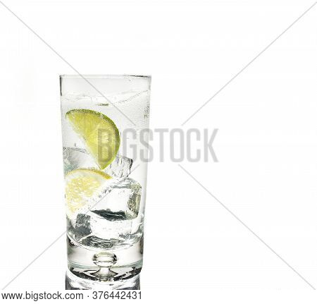 Shot Of A Glass Of Gin And Tonic With Ice And Lime  On White Background With Copy Space