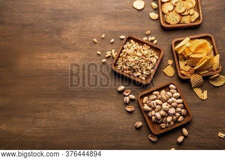 Crispy Snacks On Background. Pistachios, Nuts, Crackers, Crisps And Chips In Plate And Scattered On