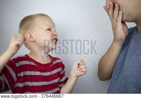 The Child Waves His Fists And Yells At His Father. Child Aggression, Family Conflicts, A Crisis Of T