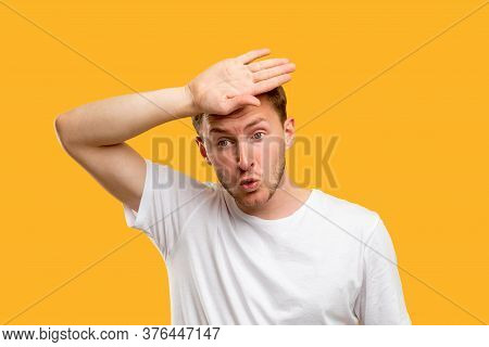 Disturbed Man Portrait. Panic Attack. Troubled Guy Touching Forehead Isolated On Orange Background.