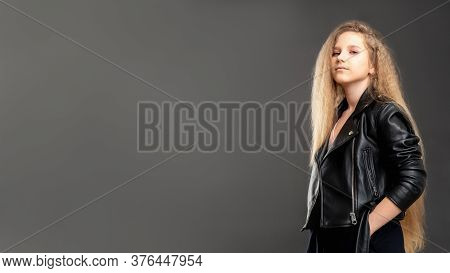 Stylish Girl Portrait. Commercial Background. Confident Young Lady In Biker Jacket Standing Isolated