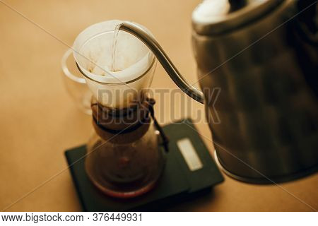 Alternative Coffee Brewing V60. Barista Making Filter Coffee On Brown Background. Pouring Hot Water