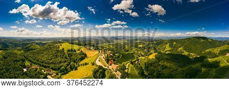 Aerial Panorama Of Of Green Hills And Vineyards With Mountains In Background. Austria Vineyards Land