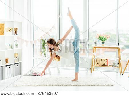 Pretty young girl doing vertical twine in bright room