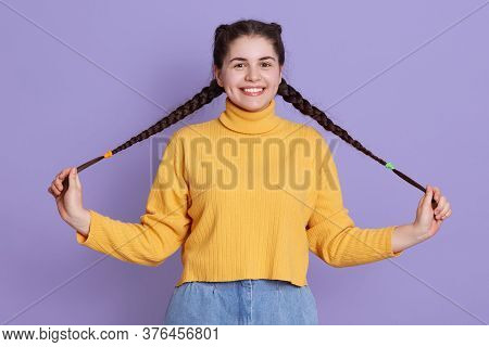 Happy Charming Lady With Two Pigtails Looking Directly At Camera And Playing With Her Hair, Posing I