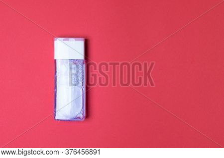 Bottle With Tonic For Health Care On Red Colored Paper Background With Copy Space.