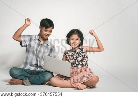 Picture Of Girl And Boy Playing Laptop. Happy Feelings, Tenderness, Care. Boy With Down Syndrome.