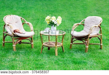Two Armchairs, Wooden Garden Furniture On Grass Lawn Outdoor For Relaxing On Hot Summer Days. Garden