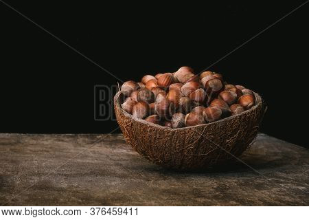 Pile Of Shelled Hazelnuts In A Coconut Shell Bowl On A Wooden Table On Black Background. Healthy Eat