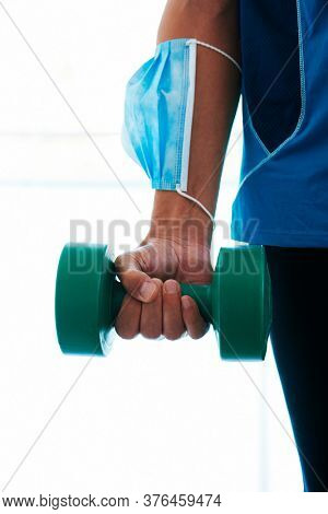 closeup of a young caucasian man in the gym, wearing sportswear, using a dumbbell and wearing his surgical mask in his arm while is not wearing it in his face