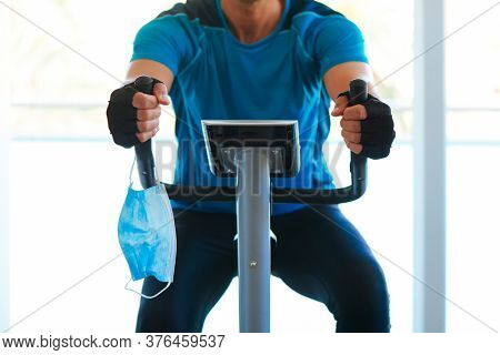 closeup of a young caucasian man in the gym, wearing sportswear, using a stationary bike, and his surgical mask holding from the handlebar while is not wearing it