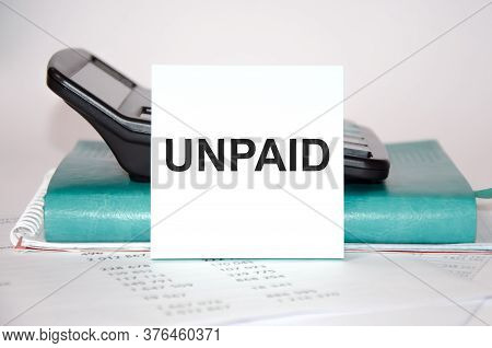 Word Unpaid Written On A Block Of Paper On The Background Of A Calculator And Notepad Close-up