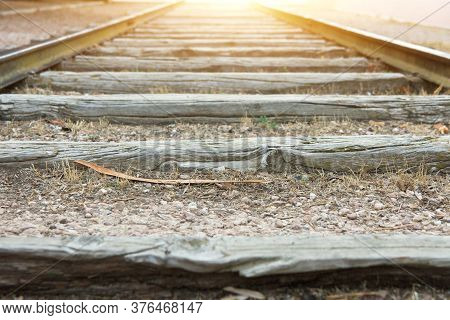Empty Old Railroad Track With Weathered Wood Planks In Perspective Golden Sunlight On Horizon Low An