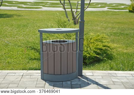 Rubbish Box In The Park . A Wooden Urn And A Comfortable Empty Park Bench . Brown Garbage Bin Inside