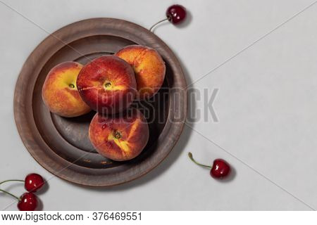 Red-yellow Peaches On A Clay Plate And A Few Cherries On A Gray Background. View From Above. Copy Sp