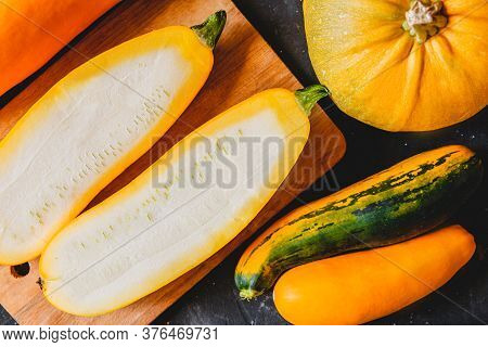 Cut Into Two Parts Zucchini On A Cutting Board On The Kitchen Table. There Are A Few More Zucchini A