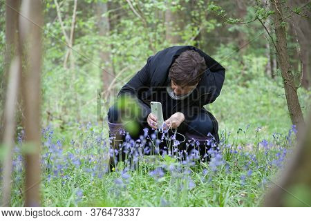 A Woman Taking Photographs Of Spring Flowers, Taken In Long Hanborough, Oxfordshire, Uk 05 05 2019