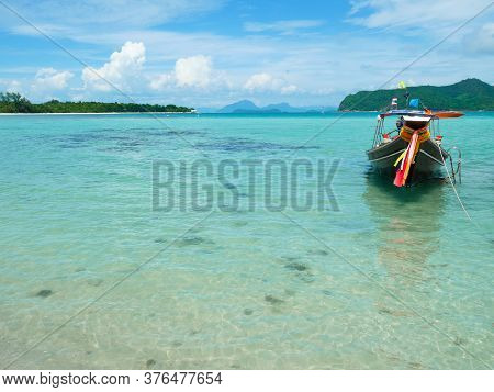 Longtail Boat On Crystal Clear Water On A Sunny Day In Koh Mudsum