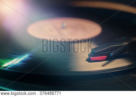 Retro Record Player With A Spinning Black Vinyl Record Reflecting Color Lights