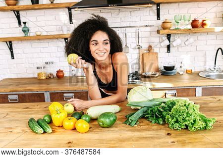 Weight Loss Diet. An African-american Woman Stands In The Kitchen Near Table Full Of Vegetables On I