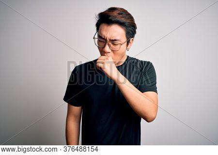 Young handsome chinese man wearing black t-shirt and glasses over white background feeling unwell and coughing as symptom for cold or bronchitis. Health care concept.