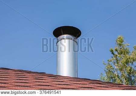 Stainless Steel Metal Chimney Pipe On The Roof Of The House Against The Sky.
