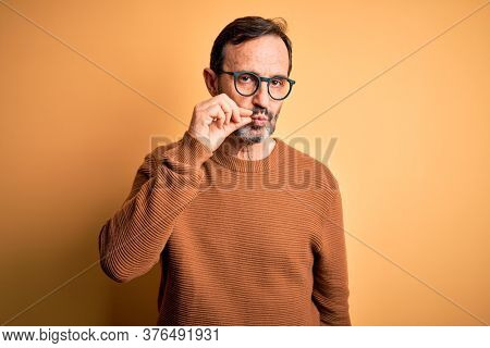 Middle age hoary man wearing brown sweater and glasses over isolated yellow background mouth and lips shut as zip with fingers. Secret and silent, taboo talking