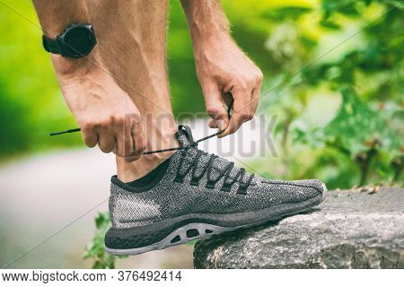 Exercise wearing heart rate tracker smartwatch sports watch man getting ready to run or walk outside lacing running shoes. Contact tracing with app connected to wearable technology.