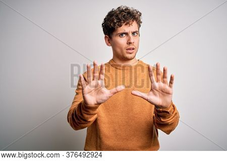 Young blond handsome man with curly hair wearing casual sweater over white background Moving away hands palms showing refusal and denial with afraid and disgusting expression. Stop and forbidden.