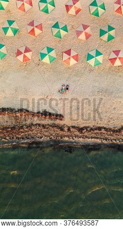 Young Couple Is Lying On A Tropical Sandy Beach Near The Ocean. Aerial View On Attractive Couple Rel