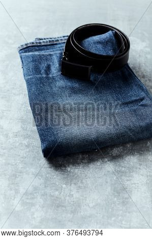 Jeans Trousers On Rustic Wooden Background. Copy Space.