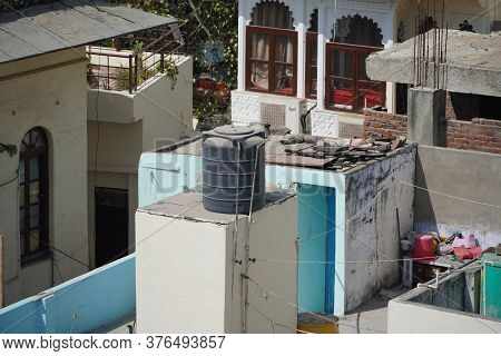 Black Water Tanks Of Industrial Building On Roof Top Or Deck Of An Old Residential Building In A Rur