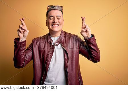 Young handsome modern man wearing fashion leather jacket and sunglasses over yellow background gesturing finger crossed smiling with hope and eyes closed. Luck and superstitious concept.