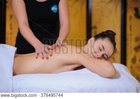 Masseur Applying Beauty Massage On A Female Client Lateral View In The Spa