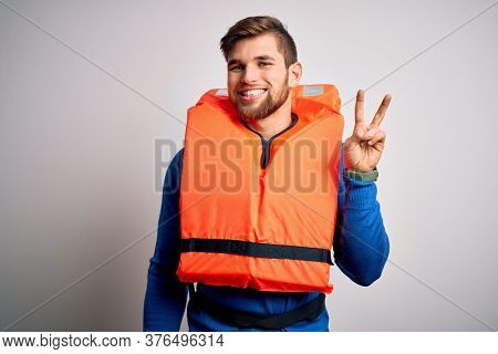Young blond tourist man with beard and blue eyes wearing lifejacket over white background showing and pointing up with fingers number two while smiling confident and happy.