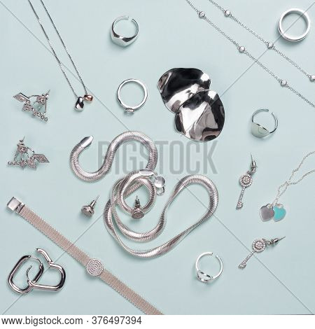 Silver Jewelry On Minimal Mint Blue Background. Rings, Bracelets And Earrings. Top View Of Fashion W