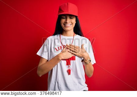 Young beautiful hispanic lifeguard woman wearing safeguard t-shirt and whistle smiling with hands on chest with closed eyes and grateful gesture on face. Health concept.