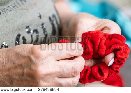 Old Female Hands Sew A Red Cloth Up Needle With A Needle