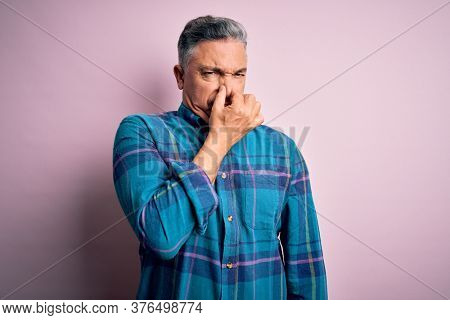 Middle age handsome grey-haired man wearing casual shirt over isolated pink background smelling something stinky and disgusting, intolerable smell, holding breath with fingers on nose. Bad smell