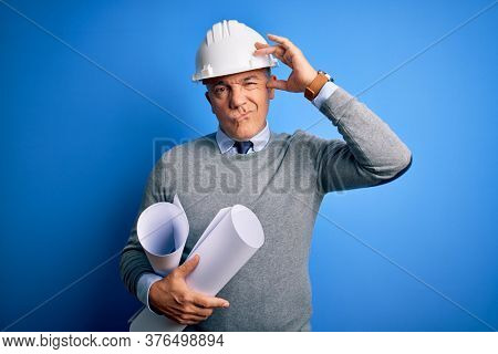 Middle age handsome grey-haired architect man wearing safety helmet holding blueprints worried and stressed about a problem with hand on forehead, nervous and anxious for crisis